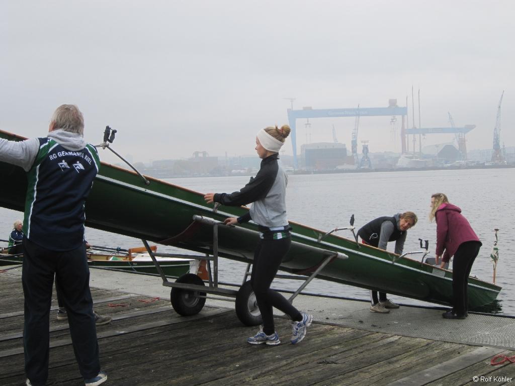 Vier Ruderer lassen ein Ruderboot am Bootssteg zu Wasser. Im Hintergrund die Portalkräne von German Naval Yards (ehem. HDW)