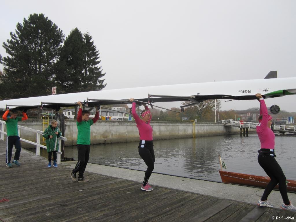 Vier Jugendliche tragen ein Rennboot über Kopf ans Wasser.