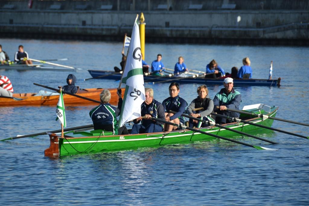 Der Steuermann eines Ruderboots mit vier Ruderern hält die Vereinsflagge der RG Germania hoch