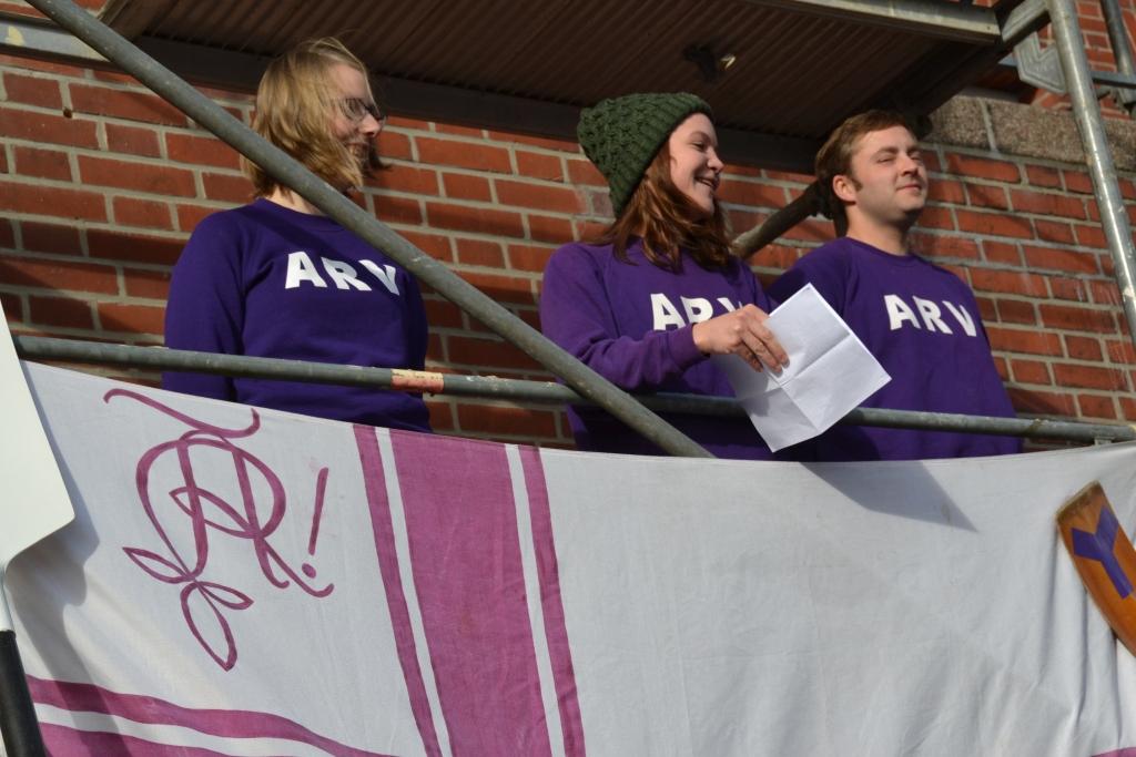 Eine Person aus einer Gruppe von drei Personen, die auf einem Baugerüst stehen. hält eine Rede, vor ihnen eine Vereinsflagge