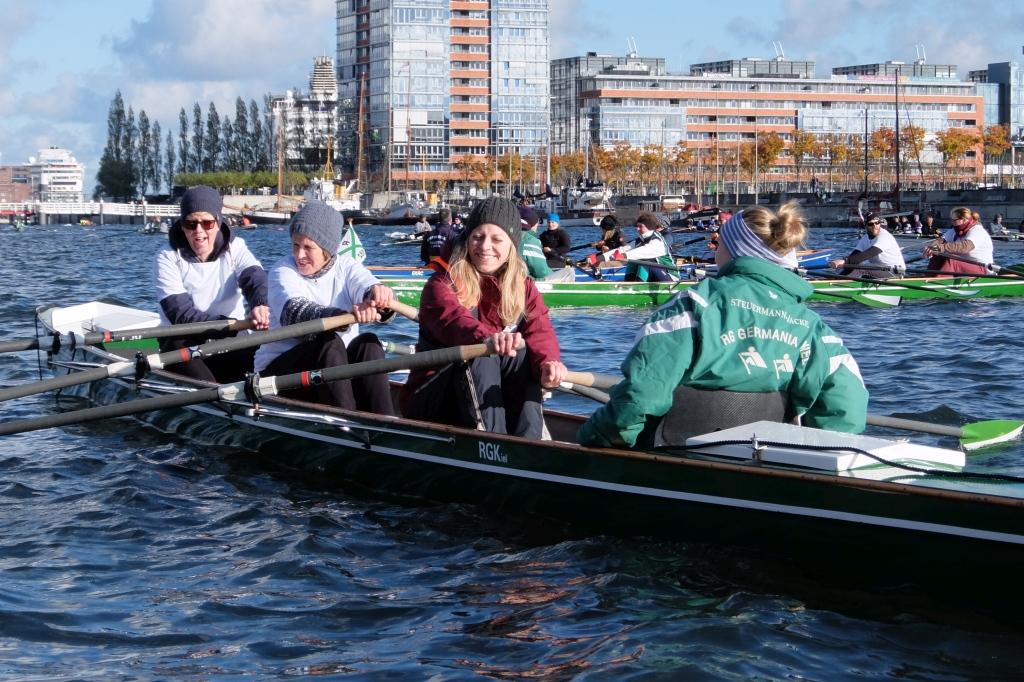 drei Ruderinnen mit Skulls in der Hand werden von einer Frau in einer Vereinsjacke gesteuert, im Hintergrund weitere Ruderboote
