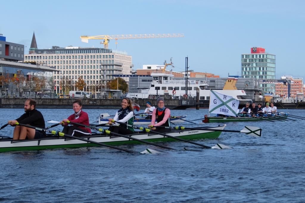 Ruderer in mehrere Ruderbooten hintereinander mit großer Vereinsfahne am Heck