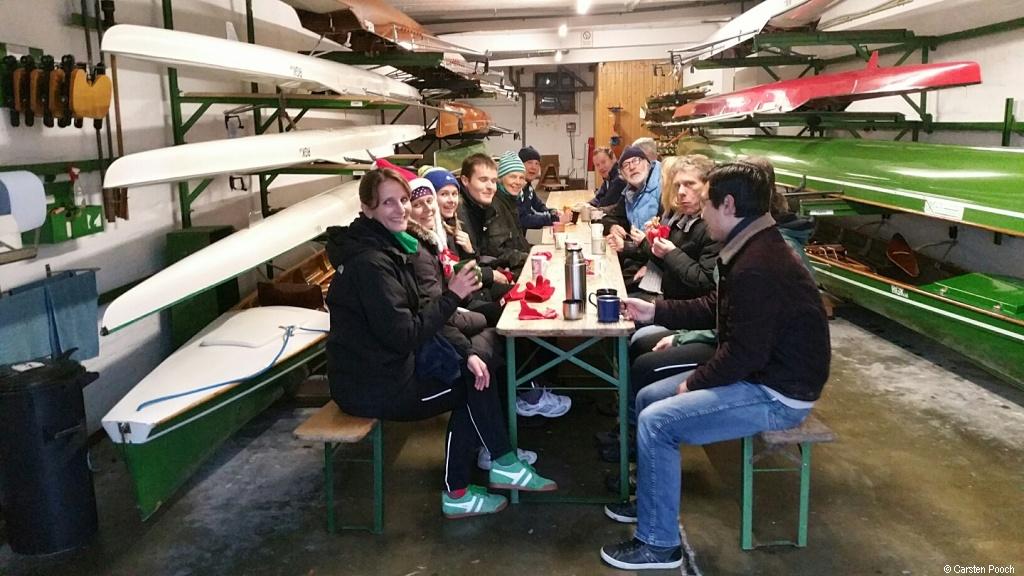 Gruppe sitzt zwischen Ruderboot im Regal an einem Tisch