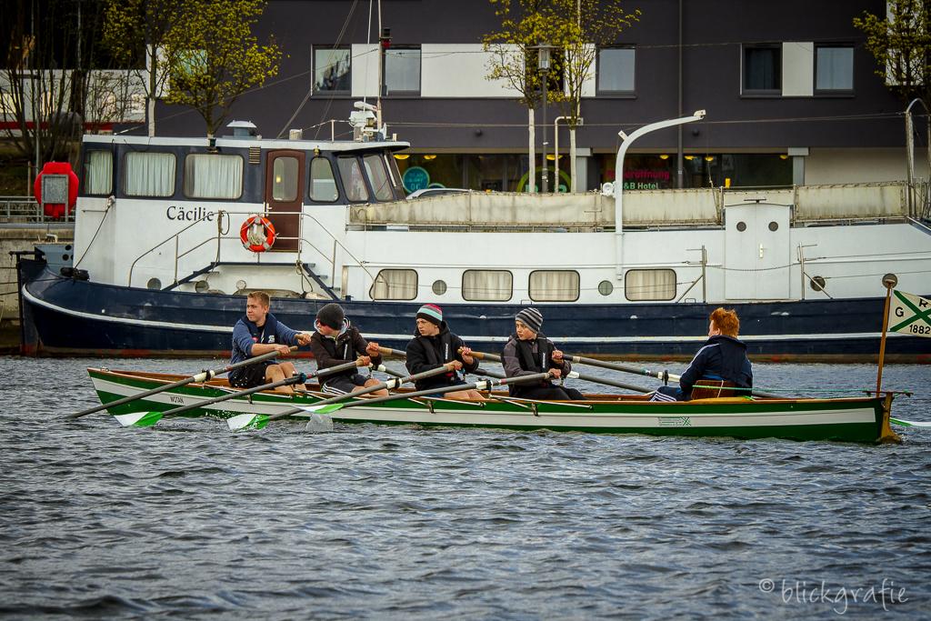 Ruderboot mit 4 jugendlichen Ruderern und Steuermann vor einer Jacht  in der Kieler Hörn