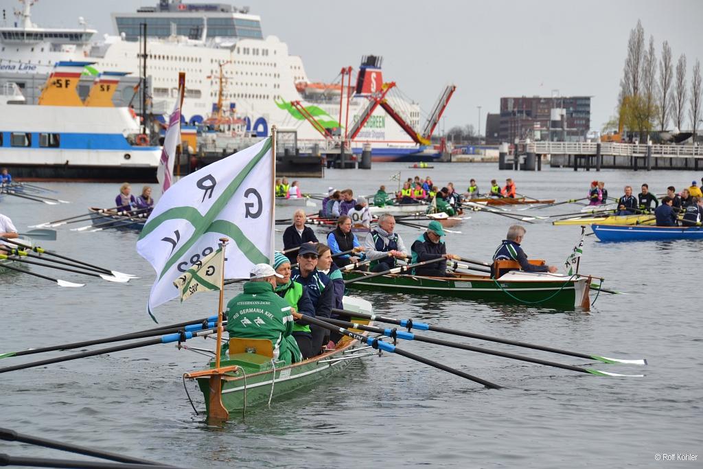Ein Mann hält in einem Ruderboot eine weiße Flagge mit gekreuzten grünen Linien hoch, dahinter viele weitere Ruderboote vor der Kieler Hörnbrücke und den großen Fähren