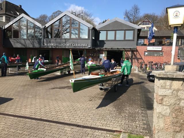 mehrere Ruderboote liegen nebeneinander auf dem Bootsplatz und werden gereinigt