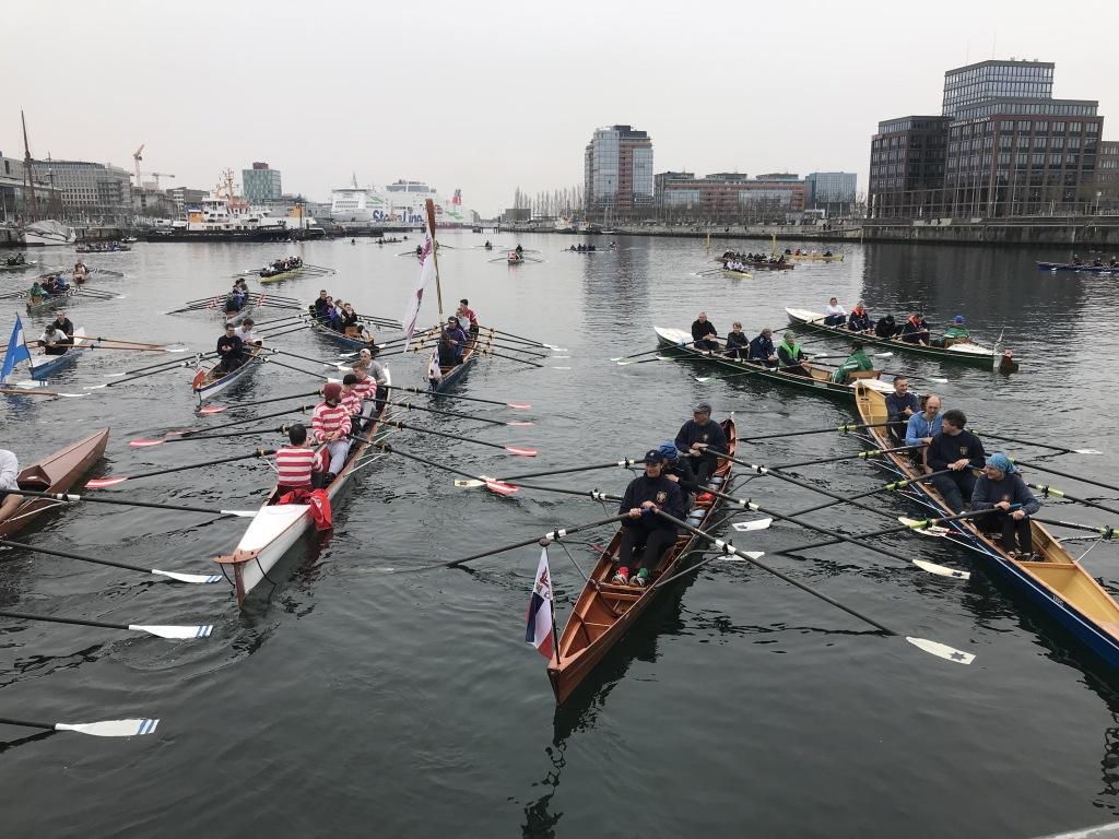 Viele Ruderboote mit Ruderern die Skulls in den Händen halten liegen vor der Kieler Hörnbrücke