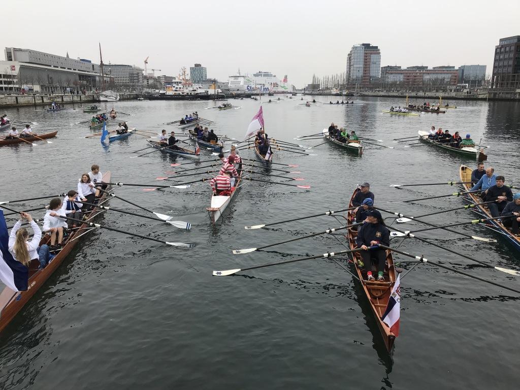 mehrere Ruderboote liegen nebeneinander und hintereinander auf dem Wasser. Ein Ruderer hält eine Vereinsfahne hoch.