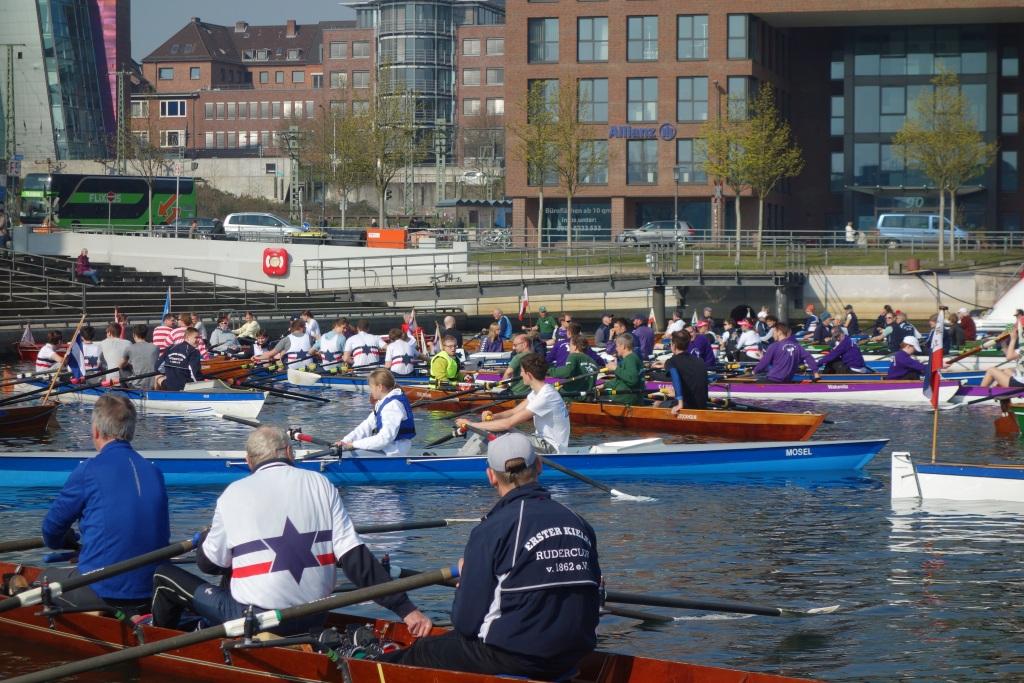 mehrere Ruderboote liegen nebeneinander und hintereinander auf dem Wasser vor der Kieler Hörn-Spitze.