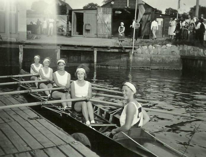 Historische Bild von 1930 mit 5 Frauen in einem Ruderboot an einem Holzsteg im Hintergrund eine Personengruppe neben einem Holzschuppen