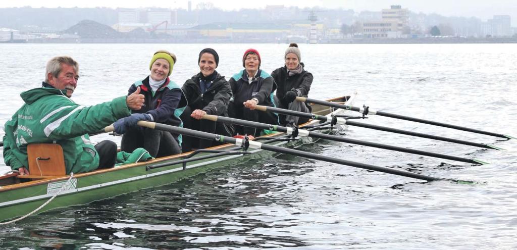 Vier Ruderinnnen lassen sich von einem Mann im Ruderboot steuern