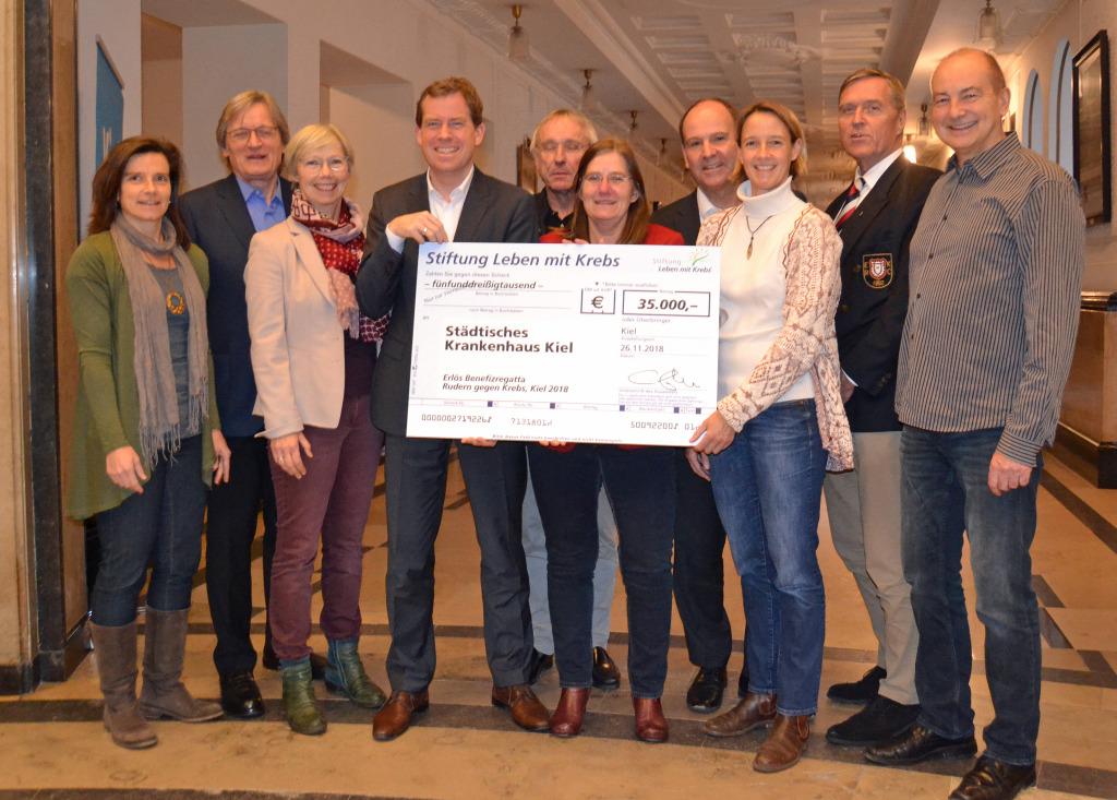 Gruppenbild mit zehn Personen, die einen großen Spendenscheck in den Händen halten