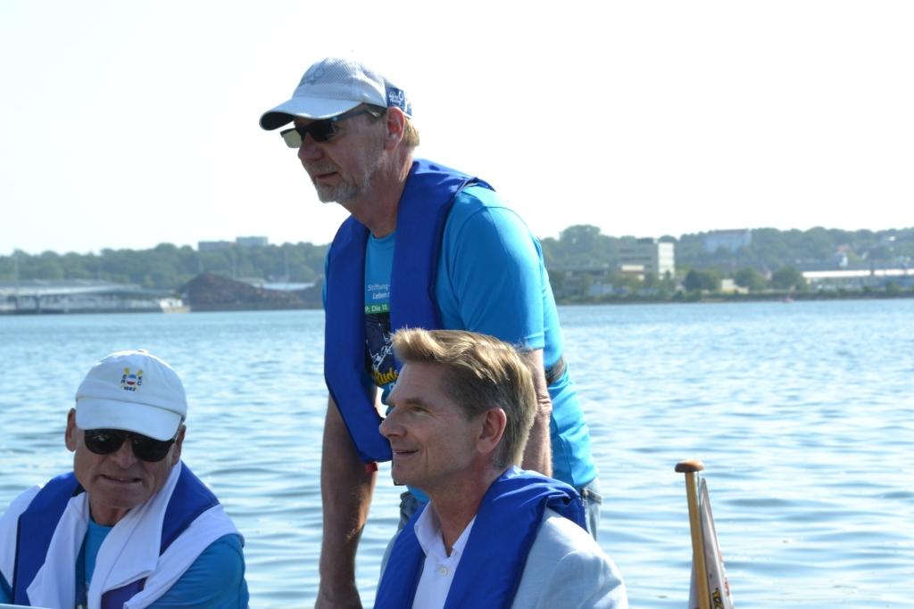 Drei Personen, zwei sitzend und einer stehend in einem Motorboot