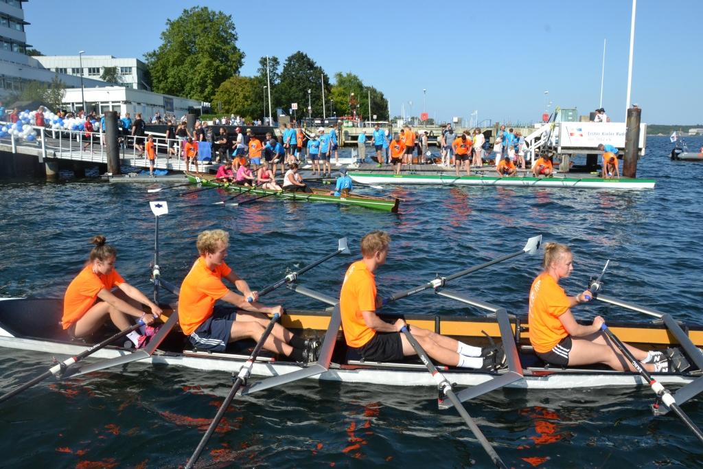 vier Schüler in orangen T-Shirts rudern vom Bootssteg weg
