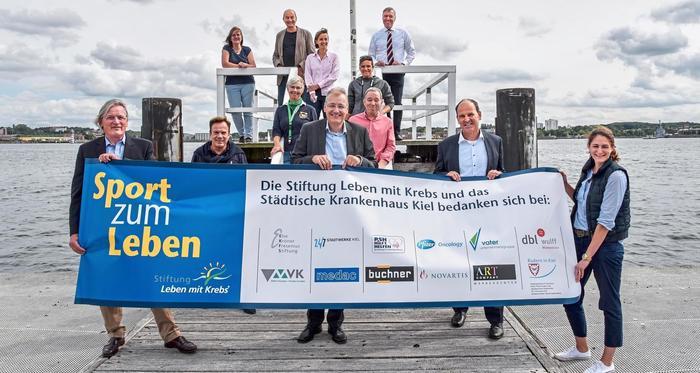 Mehrere Personen stehen auf einem Bootssteg hinter einem Werbebanner, einige davon auf einer erhöhten Holzplattform