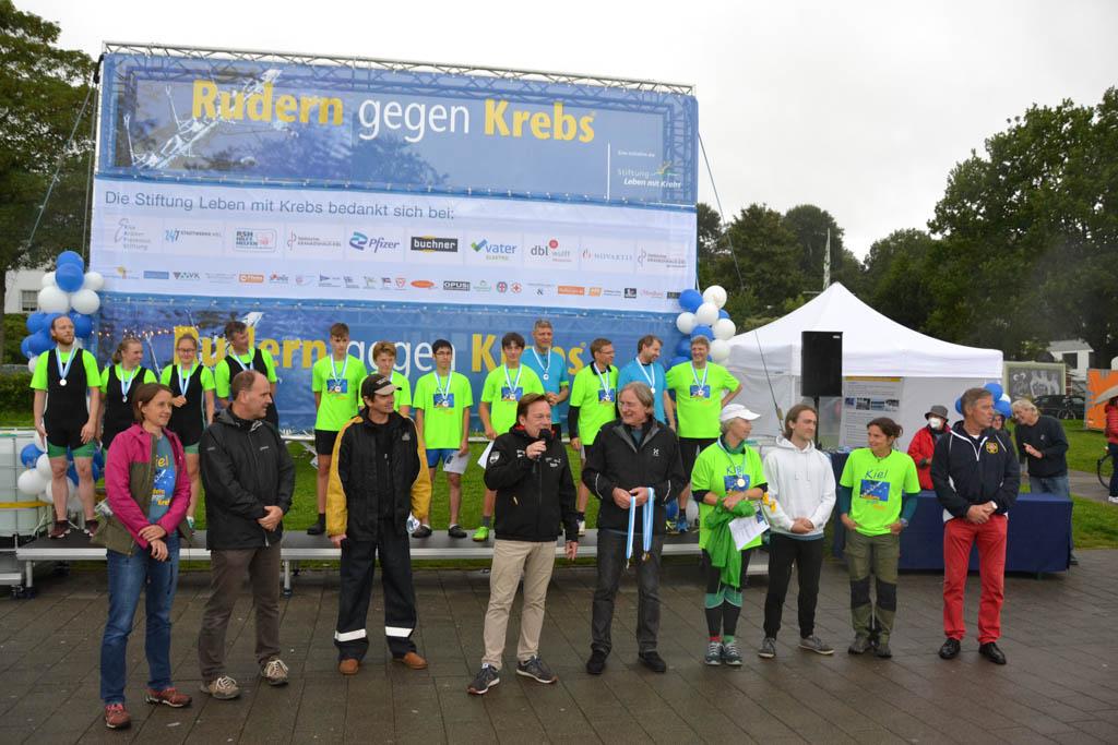 Mehrere Personen stehen nebeneinander mit einem Moderator in der Mitte vor einem Siegerpodest mit Medaillengewinnern, im Hintergrund eine große Plakatwand Rudern gegen Krebs