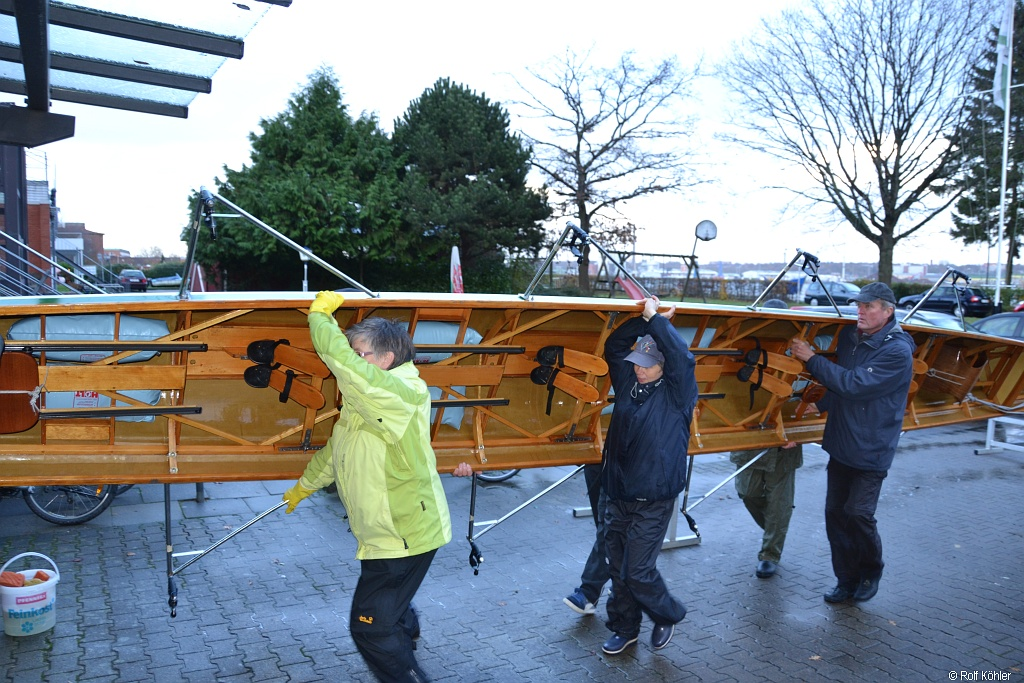 Mehrere Ruderer tragen beim Bootsdienst am 14. Nov. 2015 ein Ruderboot aufgedreht in die Bootshalle