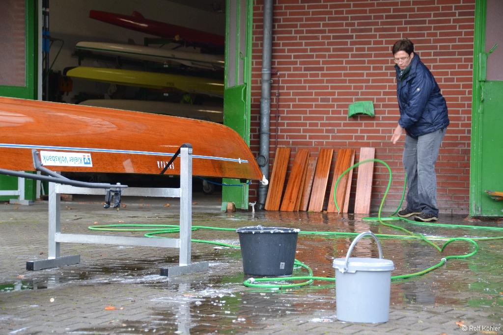 Ruderin reinigt ein Ruderboot mit einen Schlauch