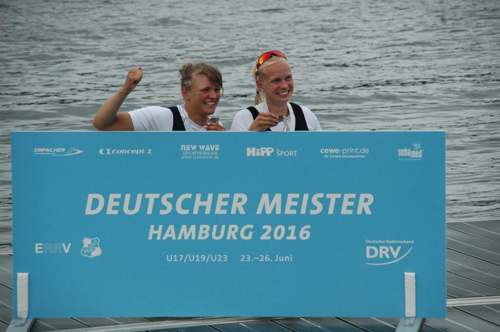 Zwei Ruderinnen stehen nach der Siegerehrung vor der Meiserschaftstafel