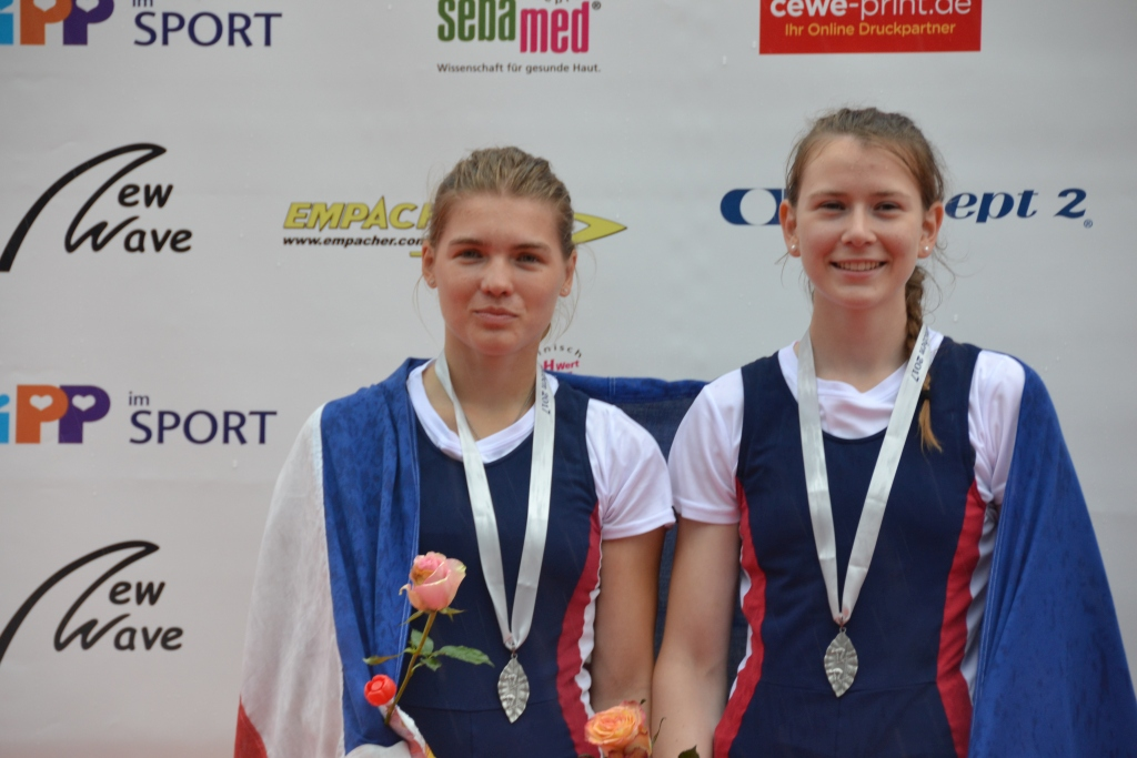 Zwei junge Mädchen mit Silbermedaille um den Hals und Rosen in der Hand vor einer Wand mit Firmenlogo