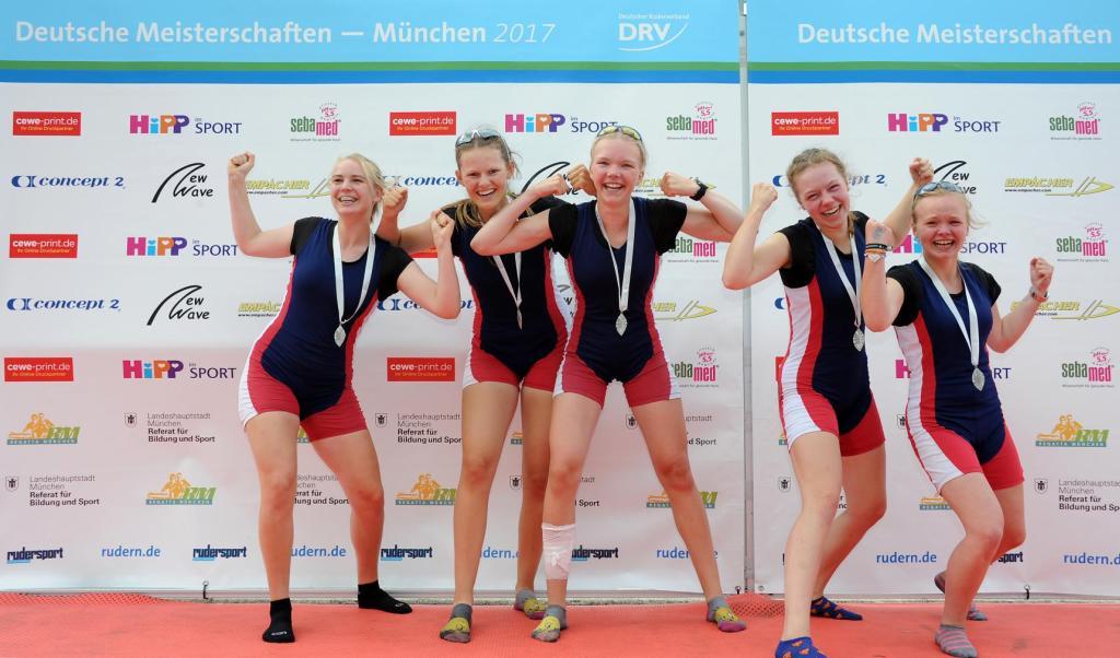 mit einer Silbermedaille um den Hals freuen sich vier junge Frauen lachend und mit gestreckten Armen