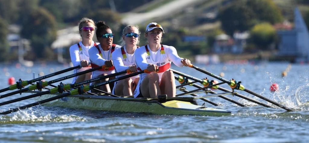 Vier Frauen sitzen hintereinander in einem Ruderboot und halten Ruderskulls in den Händen
