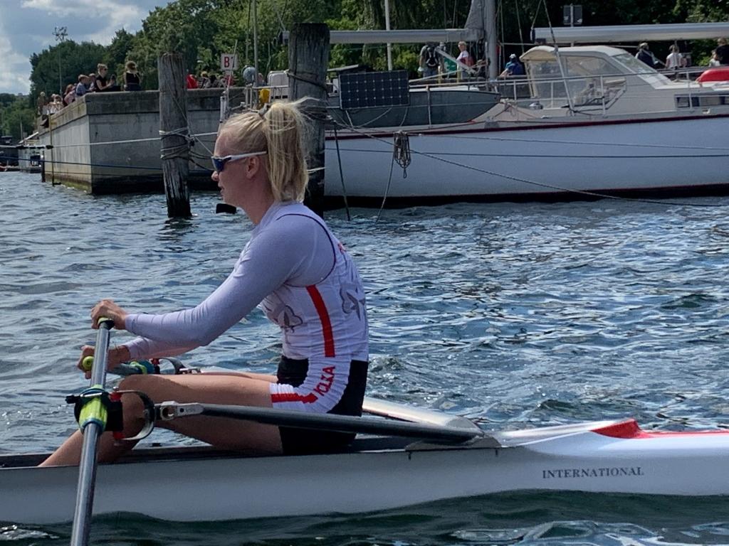 Junge Frau sitzt in einem schmalen Ruderboot und hält Skulls in den Händen