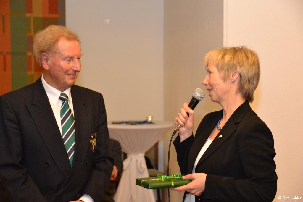 Sabine Köhler spricht Dankesworte in ein Mikrofon und überreicht Uwe Zwingmann ein Buchgeschenk