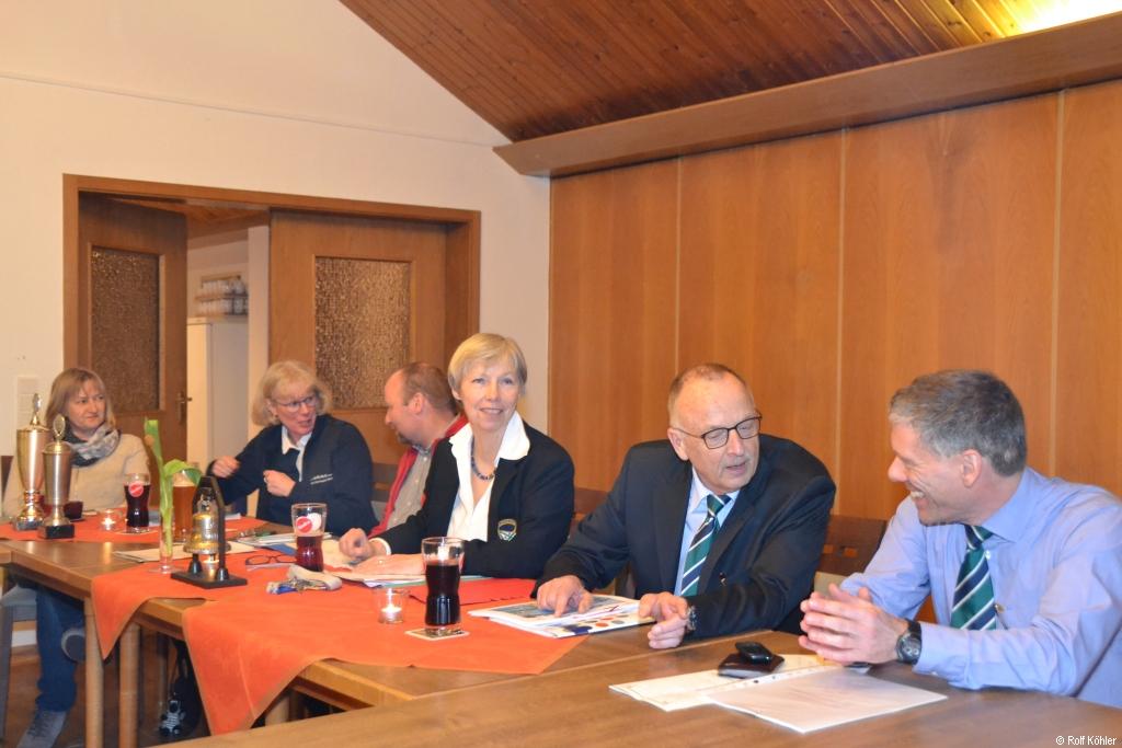 Mehrere Personen sitzen hinter einer Tischreihe
