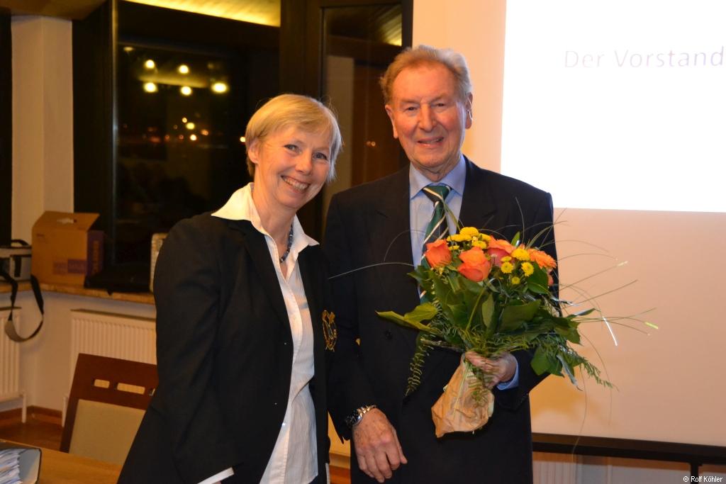Zwei Personen: Mann mit Blumen in der Hand und Frau lächeln