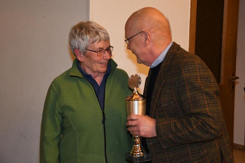 Eine Frau bekommt für ihre sportlichen Erfolge von einem Mann einen Pokal ausgehändigt
