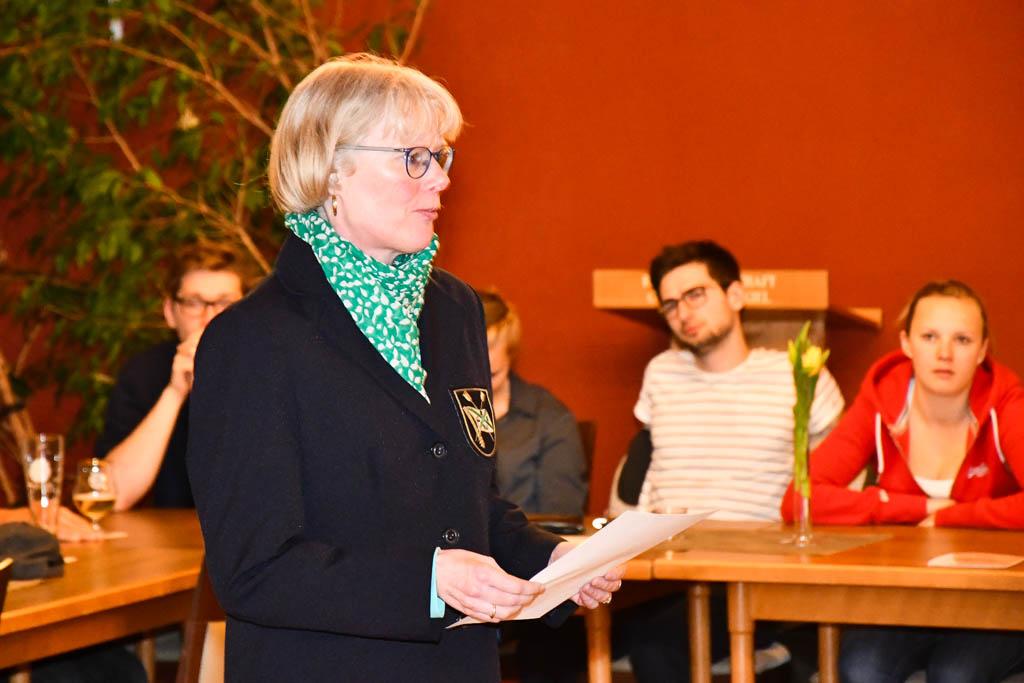 Eine Frau steht mit einem Zettel in Hand vor einer Tischreihe hinter der mehrere Personen sitzen