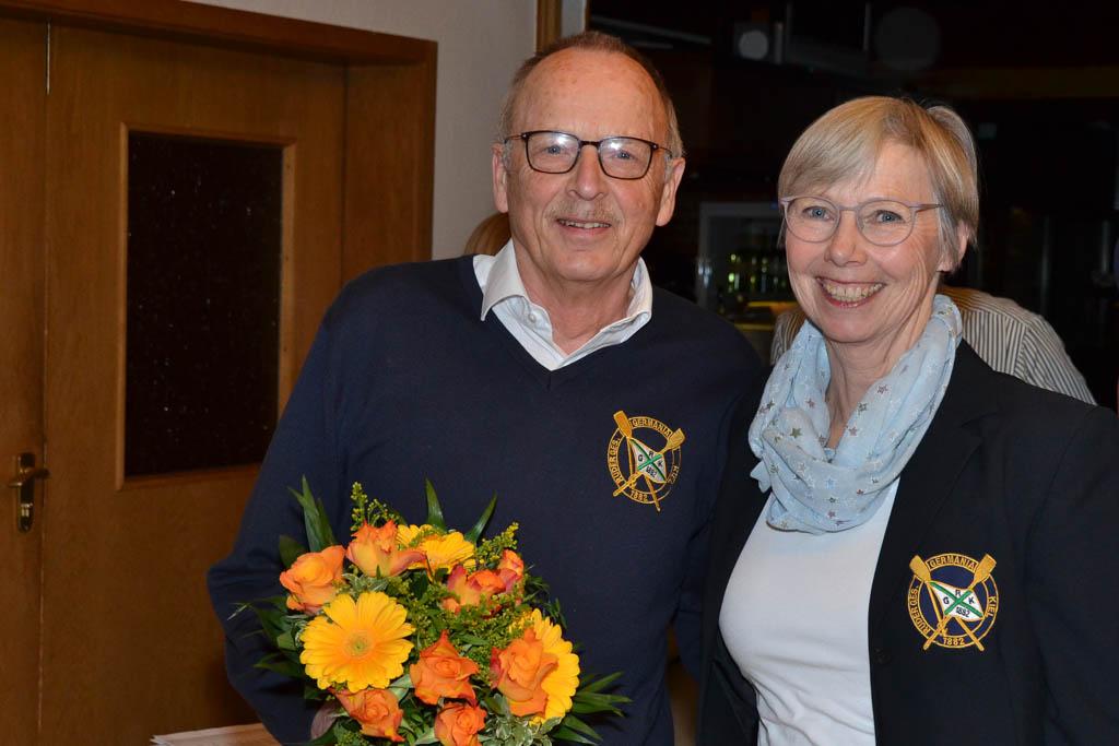 Ein Mann mit einem Blumenstrauß in der Hand und eine Frau stehen lächelnd nebeneinander