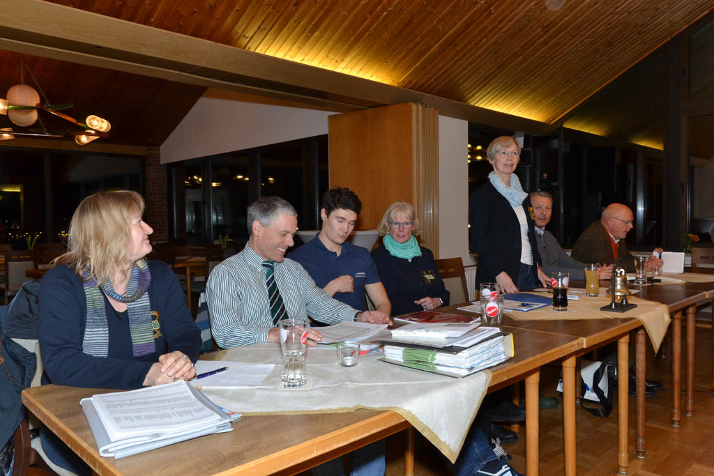 Eine Gruppe von Personen sitzt hinter Tischen mit Akten darauf. Eine Frau steht und redet.
