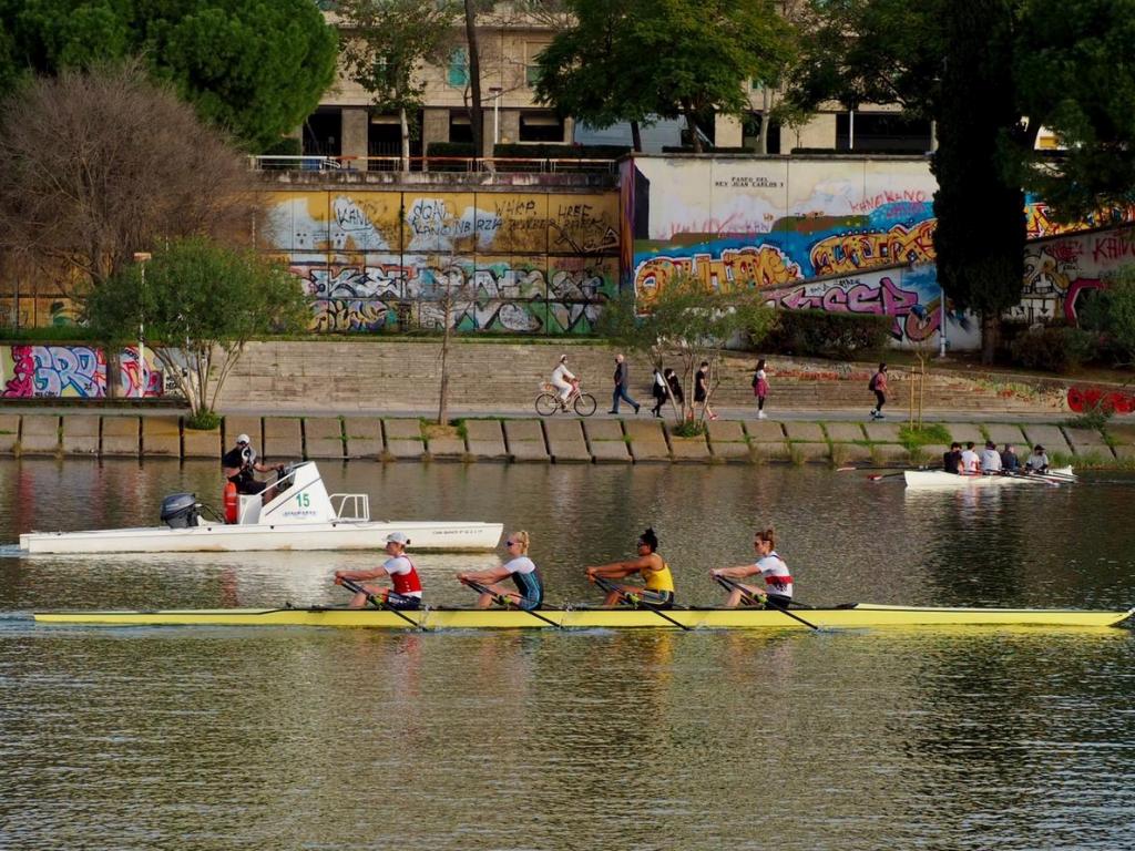 Vier Frauen sitzen hintereinander im Ruderboot, dahinter ein Motorboot