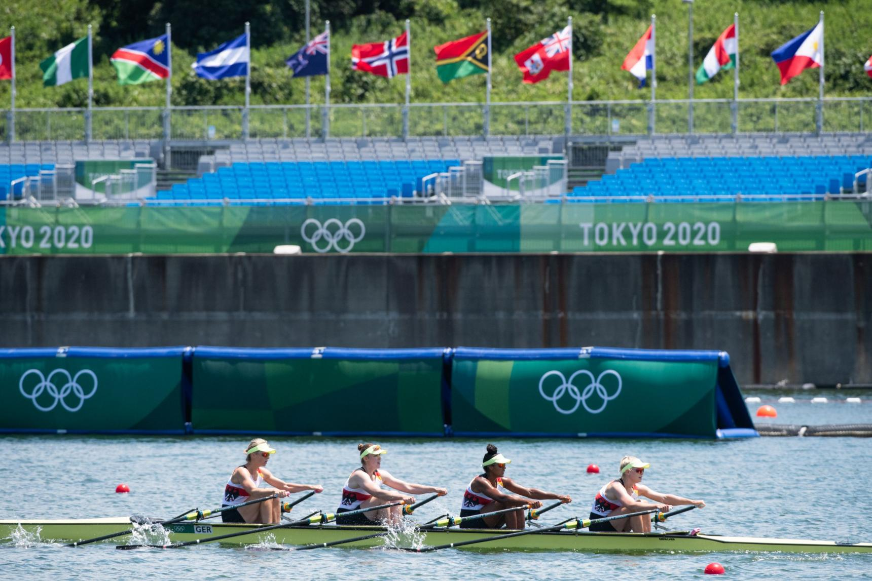 Vier Frauen in einem gelben Ruderboot vor einer leeren Zuschauertribüne mit Olympischen Ringen Tokyo 2020 und vielen Länderfahnen