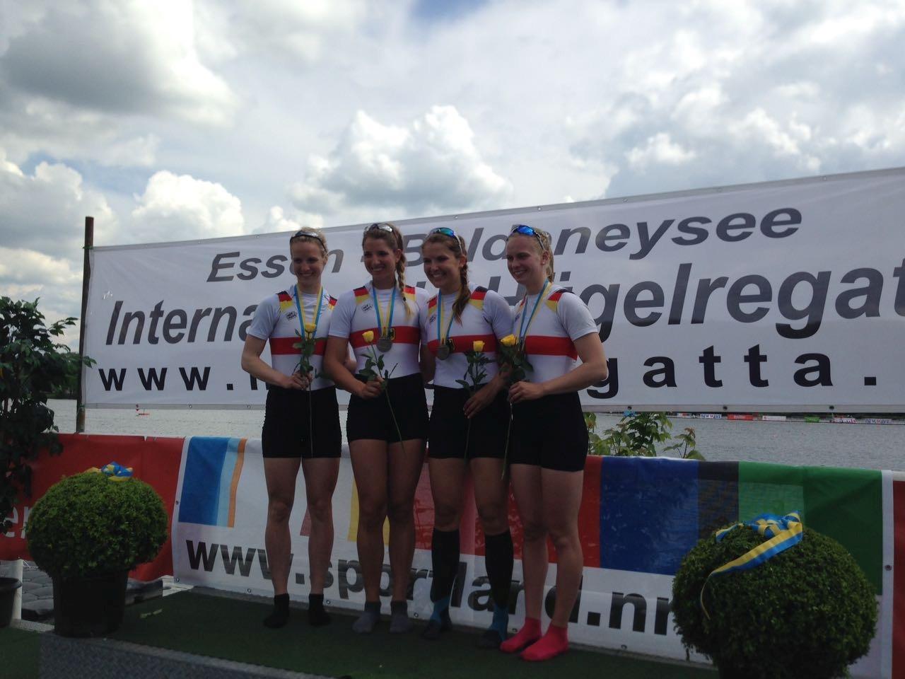Vier Ruderinnen stehen bei der Siegerehrung auf dem Podest