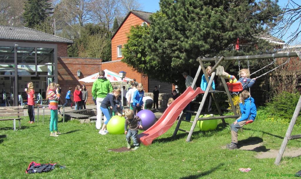 Kinder spielen mit Peziball und auf der Rutsche