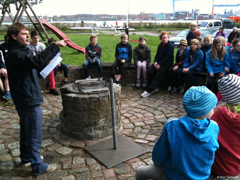 Jugendleiter Tim Schreiber erklärt Kindern das Rudern.