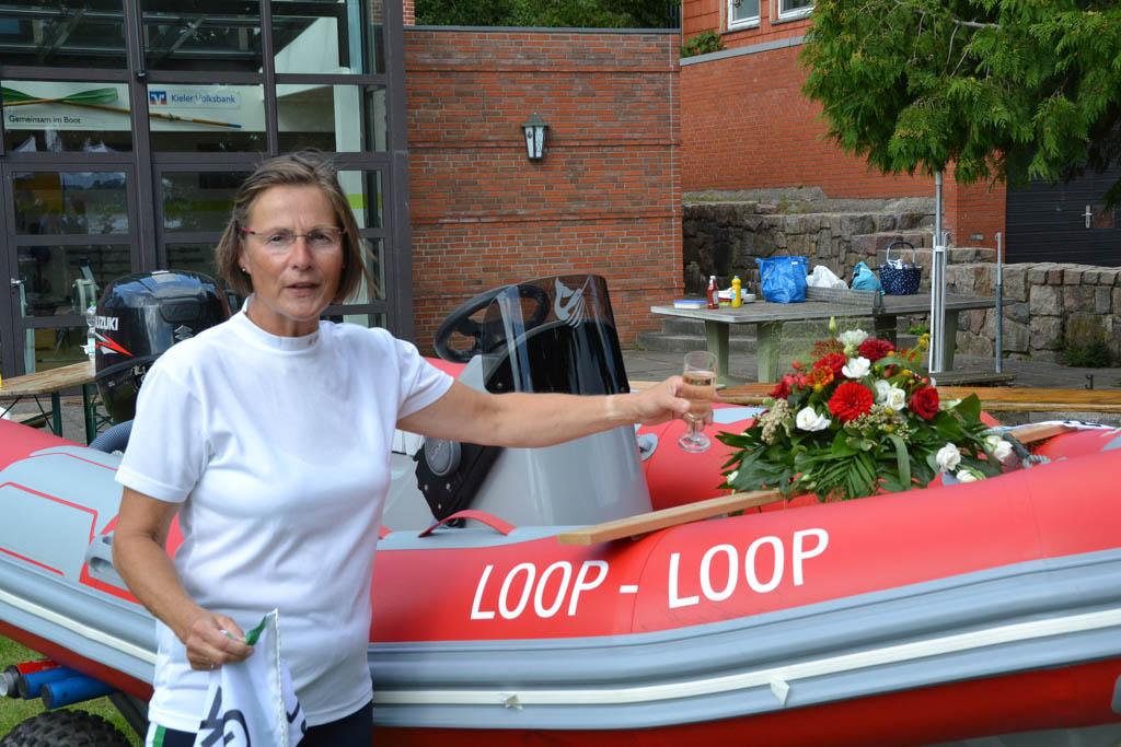 Frau steht mit Sektglas in der Hand vor einem roten Motorboot