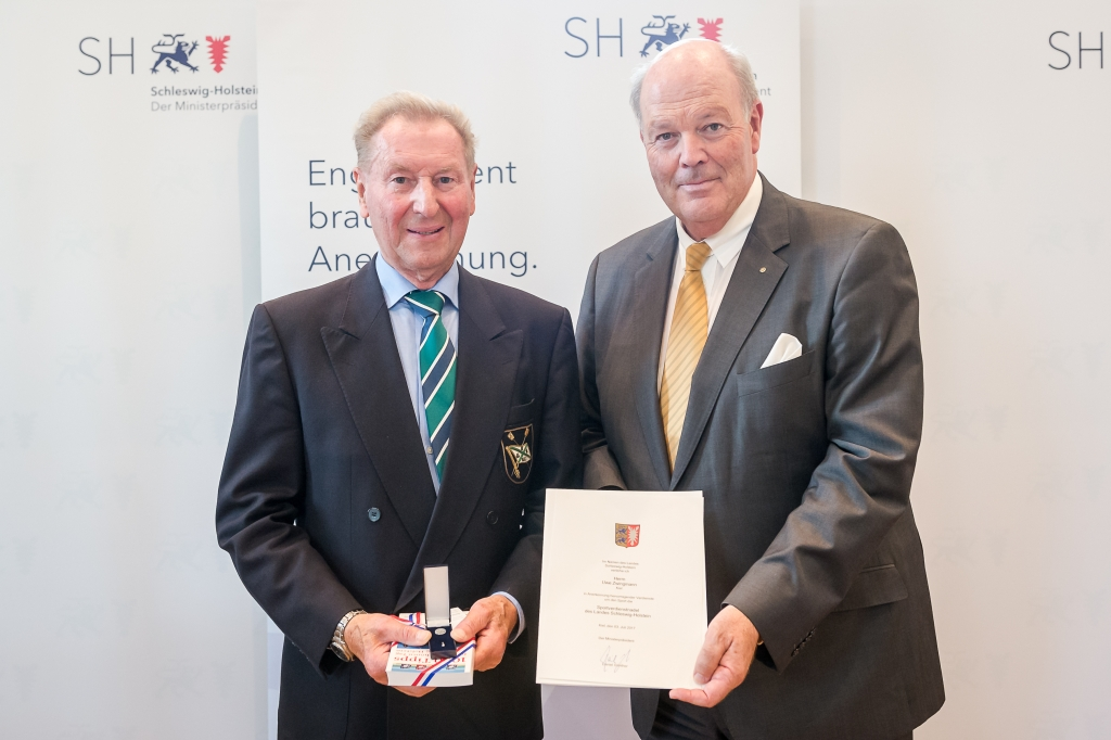 Zwei Herren nebeneinander mit Urkunde und Verdienstnadel in der Hand