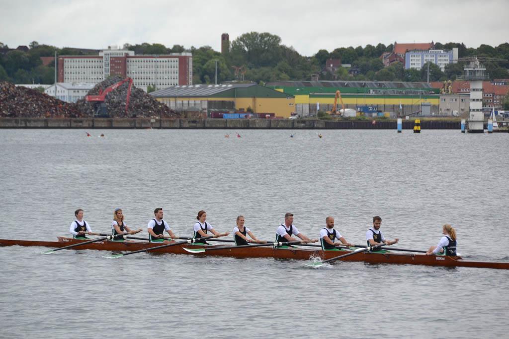 Ein Ruderboot auf dem Wasser mit 9 Frauen und Männern an Bord