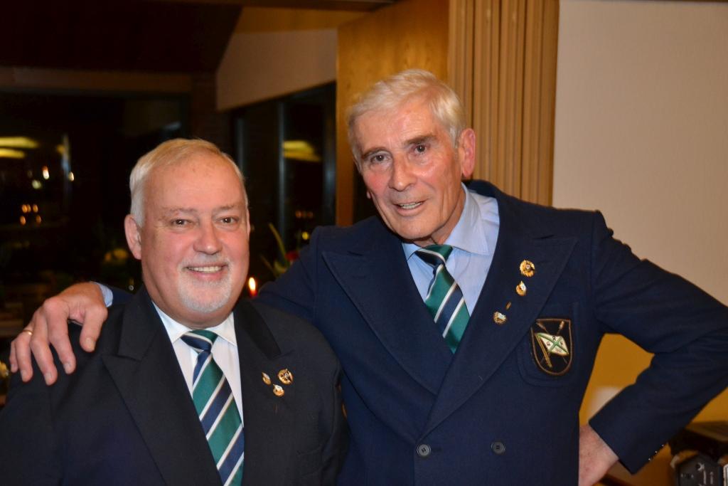 ein älterer Herr legt sein Arm um ebenfalls alten Herrn, beide tragen Ehrennadeln am Revers für ihre 60-jährige Vereinsmitgliedschaft