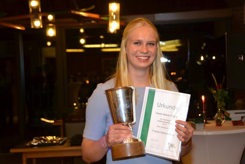 junge Frau, beste Sportlerin 2017, hält Pokal und Urkunde in der Hand