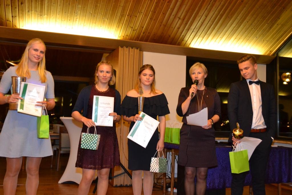 Gruppenbild mit mehreren Personen, die für ihre sportlichen Leistungen Pokale und Urkunden in den Händen halten, zweite von rechts mit Mikrofon die 1. Vorsitzende Sabine Köhler
