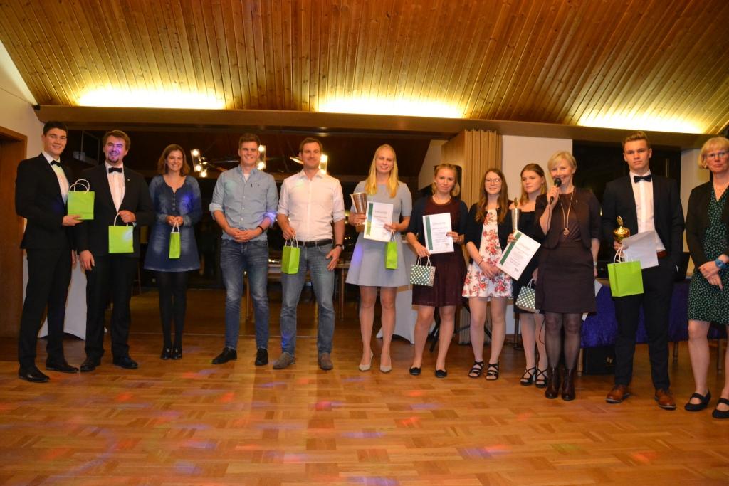 Gruppenbild mit mehreren Personen, die Urkunden und Pokale oder Geschenktüten in den Händen halten, dritte von rechts mit Mikrofon die 1. Vorsitzende Sabine Köhler