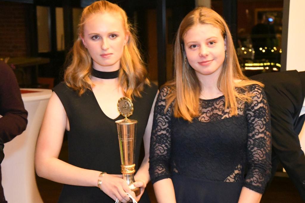 zwei junge Frauen, die linke mit einem Pokal in der Hand, stehen nebeneinander