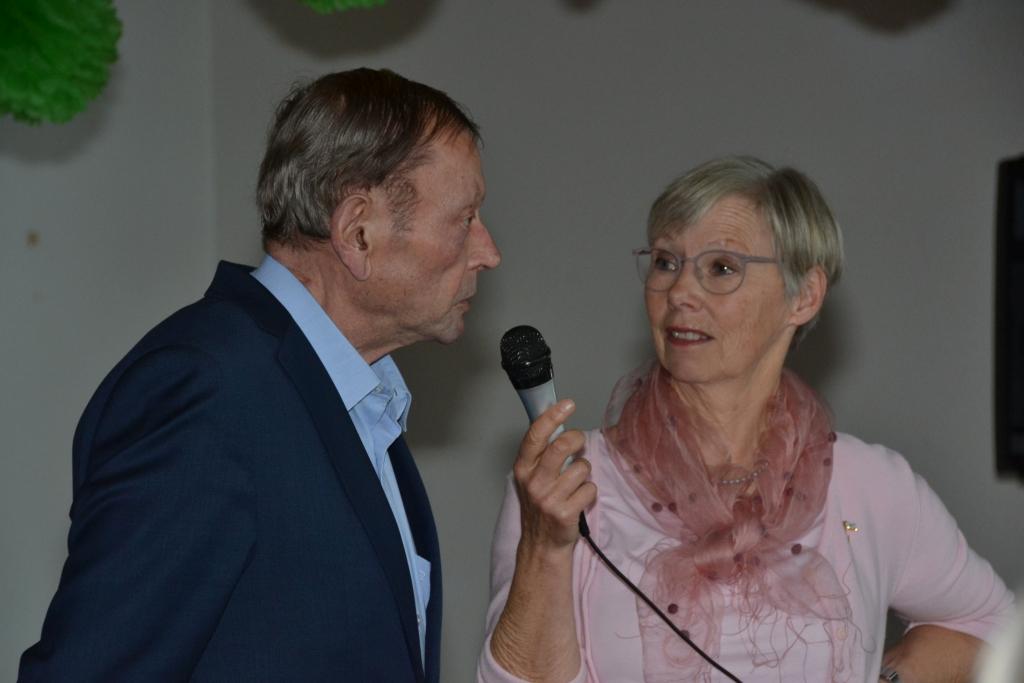 Eine Frau hält einem Man für ein Interview ein Mikrofon vor den Mund