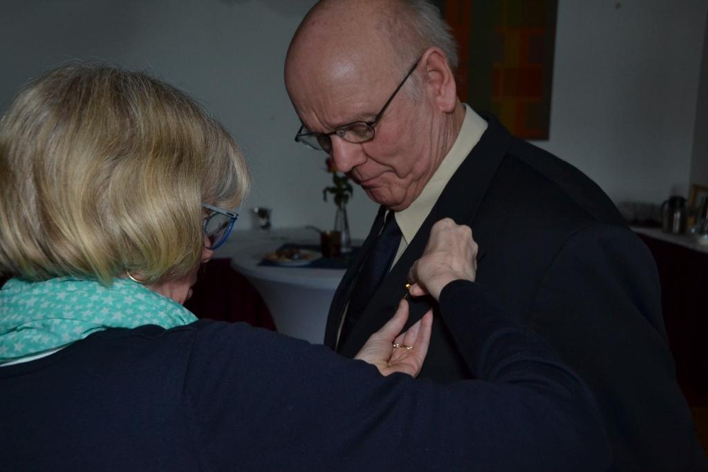 Eine Frau steckt einem Man ein Ehrenzeichen ans Revers