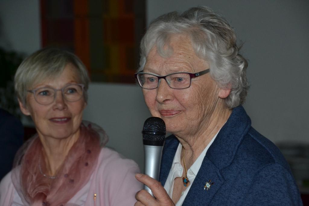 eine ältere Frau mit Brille hält ein Mikrofon in der Hand, im Hintergrund schaut eine Frau interessiert zu